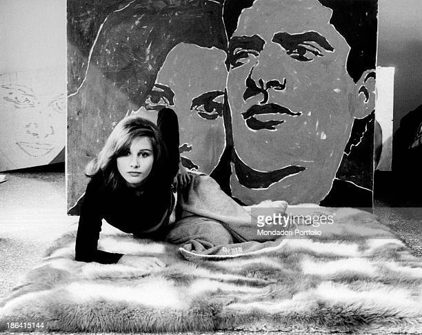 Italian actress Paola Pitagora posing at home in front of a double portrait by her Italian partner and artist Renato Mambor Rome 1966