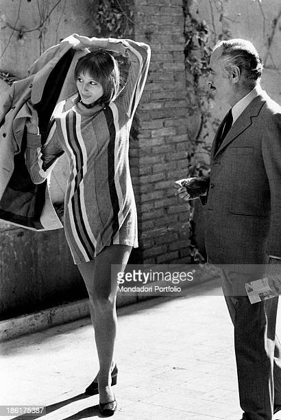 Italian actress Paola Pitagora putting on a jacket on the film set of The True and the False Beside her American actor Martin Balsam smoking a...