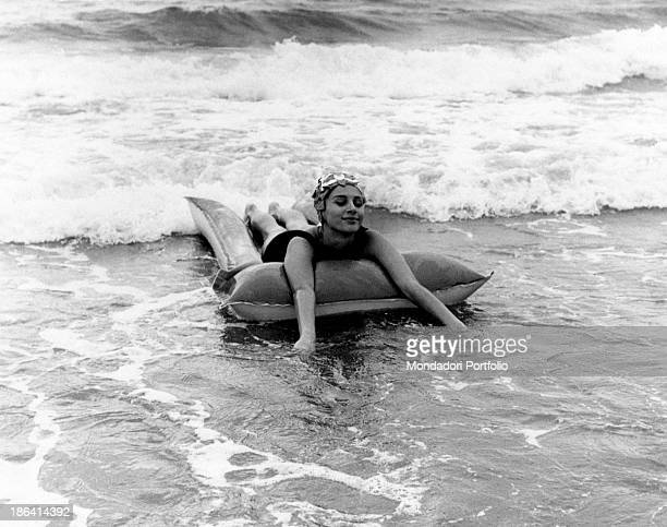 Italian actress Paola Pitagora relaxing on an air bed wearing onepiece swimsuit and bathingcap 1962