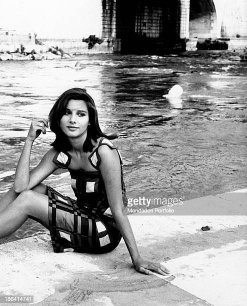Italian actress Paola Pitagora sitting by the Tiber River on the Tiber Island. Rome, 1966.