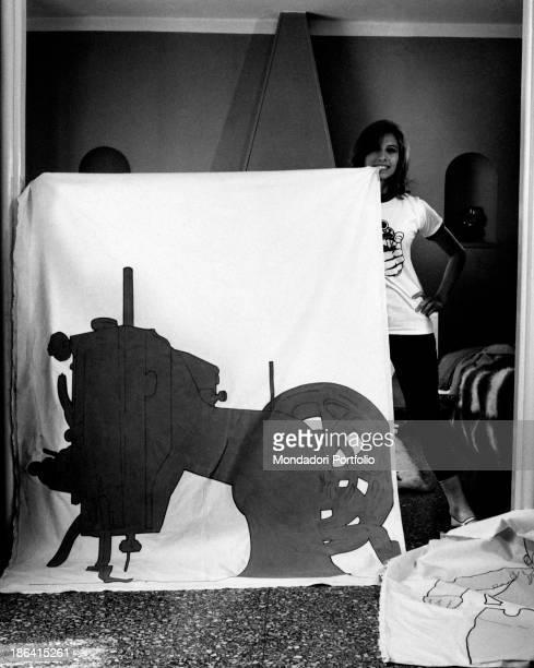 Italian actress Paola Pitagora smiling at home beside a silkscreen printing by her Italian partner and artist Renato Mambor Rome 1966