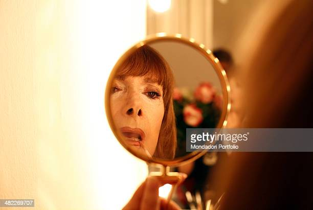 Italian actress Rossella Falk is portrayed in a closeup faced backwards while applying makeup on her lips in her changing room at Teatro Manzoni the...