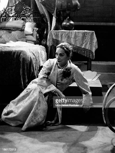 Italian actress Sarah Ferrati sitting at the foot of a bed in the play La folle de Chaillot Milan March 1954