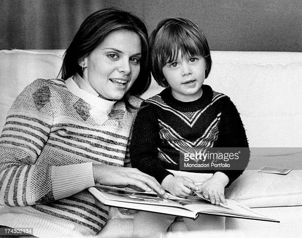 Italian actress Silvia Dionisio reading a book on the sofa with her son and Italian actor Saverio Deodato Dionisio Rome 1970s