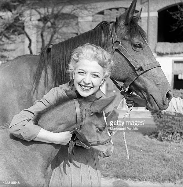 Italian actress smiles at the camera while posing between a horse and a colt she hugs with tenderness star of the musical theatre of the Italian...