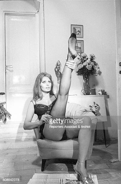 Italian actress Sophia Loren as a prostitute undressing taking off her nylon stockings while seating on an armchair on the set of the film 'Yesterday...