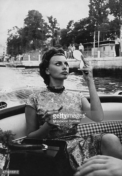 Italian actress Sophia Loren checking her makeup with a mirror on board a boat during the 19th Venice International Film Festival Venice August 1958
