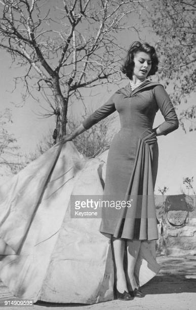 Italian actress Sophia Loren holds a red cape during a lesson from famous bullfighter Luis Miguel Dominguin at his private training ring at the Villa...