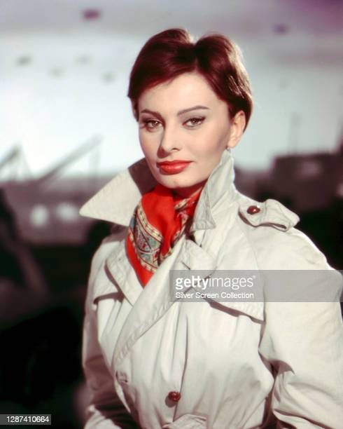 Italian actress Sophia Loren in a trench coat and scarf during the filming of 'The Key', 1958.