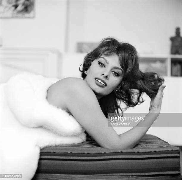 Italian actress Sophia Loren is lying on her belly holding her head up and playing with her hair while looking at the camera. She is wearing a white...
