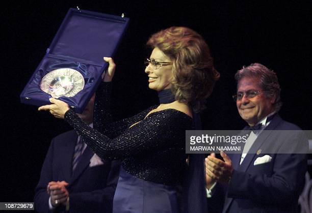 Italian actress Sophia Loren shows her gift to the audience after she was honored at the opening ceremony of Egypt's 24th International Film Festival...