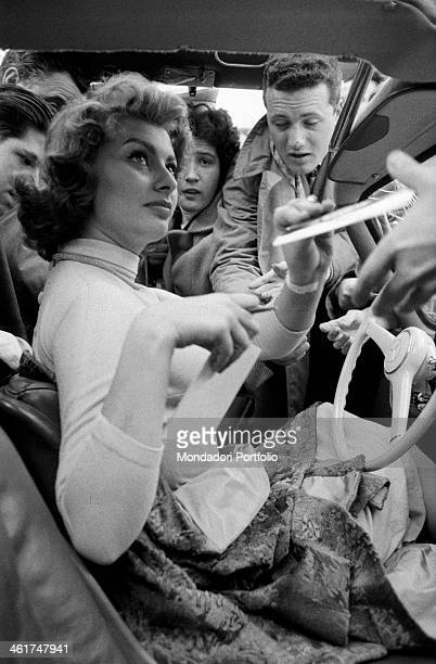 Italian actress Sophia Loren signing autographs seated into her Mercedes The actress is taking part in third Cinema Rally Bologna 1956