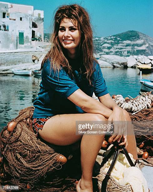 Italian actress Sophia Loren sits on a pile of fishing nets in a a small harbour circa 1965