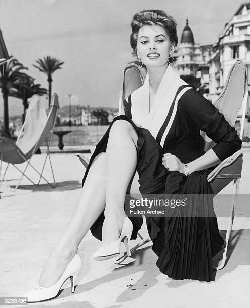 Italian actress Sophia Loren sits outdoors in a butterfly chair on the beach at Cannes wearing a dark dress with a pleated skirt and white high heels
