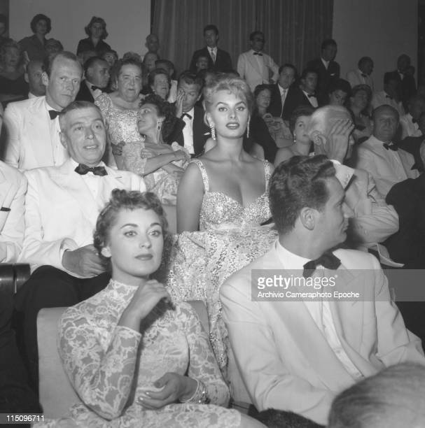 Italian actress Sophia Loren sitting among the audience in a cinema wearing an evening dress and jewelery earrings Elsa Maxwell sitting two rows...