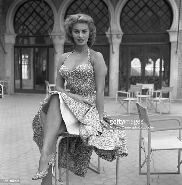 Italian actress Sophia Loren sitting on a chair wearing a floral dress Venice 1955