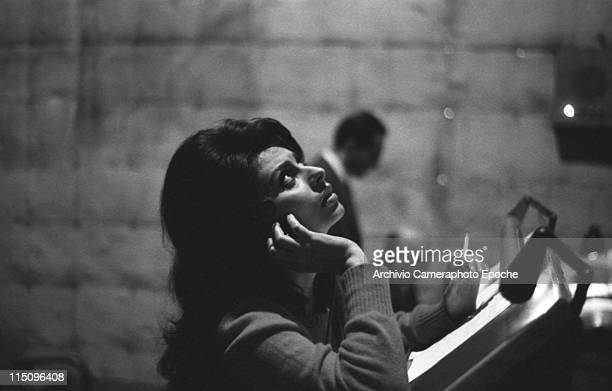Italian actress Sophia Loren smoking a cigarette dubbing the movie 'El Cid' wearing a pullover holding headphones Rome 1961