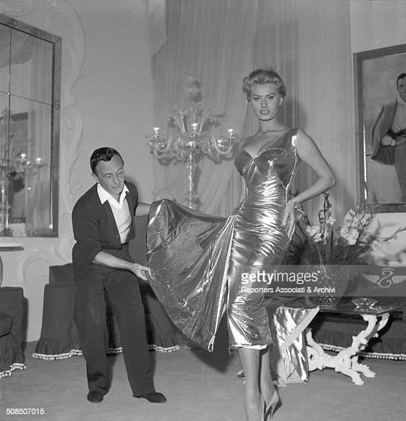 Italian actress Sophia Loren tries on a dress with fashion designer Emilio Schuberth in his studio 1955