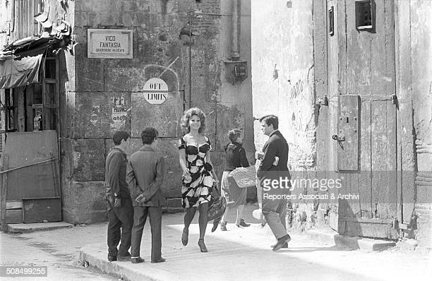 Italian actress Sophia Loren walking in a street in the film 'Marriage Italian Style' Italy 1964 Around her some men staring at her