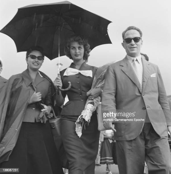 Italian actress Sophia Loren walking with her sister Anna Maria under a black umbrella because of the rain Lido Venice 1950
