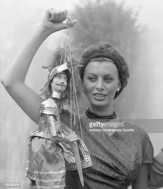 Italian actress Sophia Loren wearing a fancy dress a headband a beads necklace and pearl earrings holding a sicilian string puppet in her right hand...