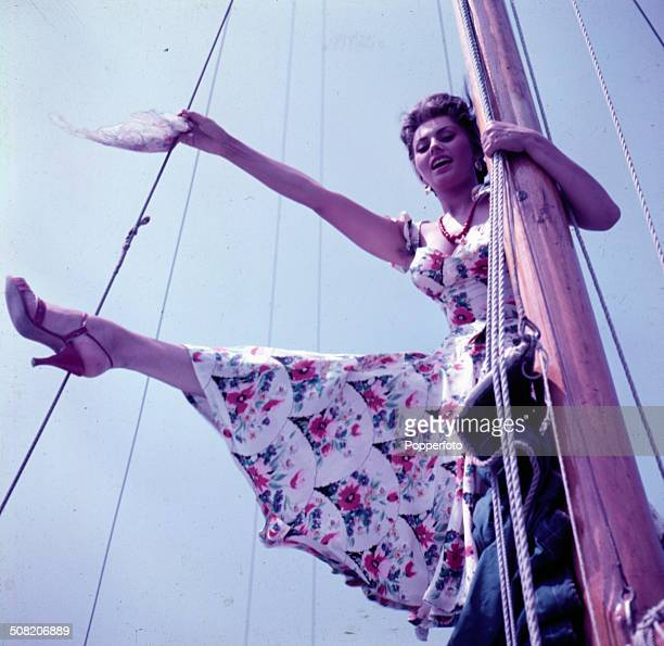 Italian actress Sophia Loren wearing a floral patterned dress poses holding on to the mast of a yacht in 1965