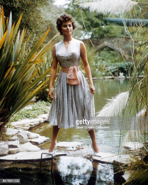 Italian actress Sophia Loren wearing a white dress with pastel pink belt circa 1960