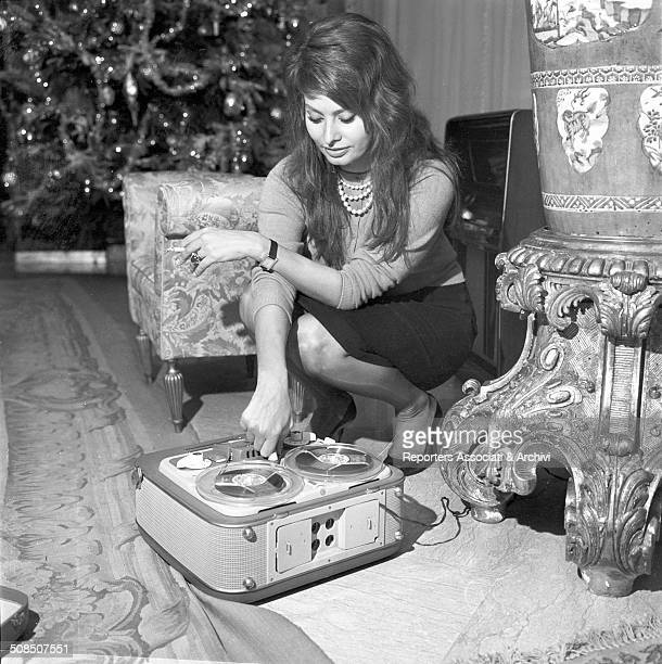 Italian actress Sophia Loren with a cassette player at her home during the Christmas period 1960