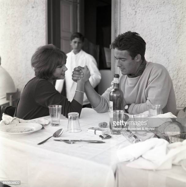 Italian actress Stefania Sandrelli and French actor Jacques Charrier doing arm wrestling in a restaurant 1965