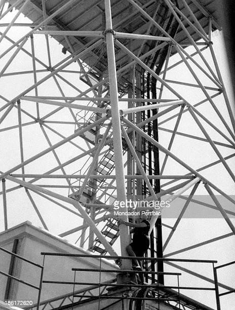 Italian actress Tatiana Farnese climbing the supporting tower of the TV bridges Rome 1959