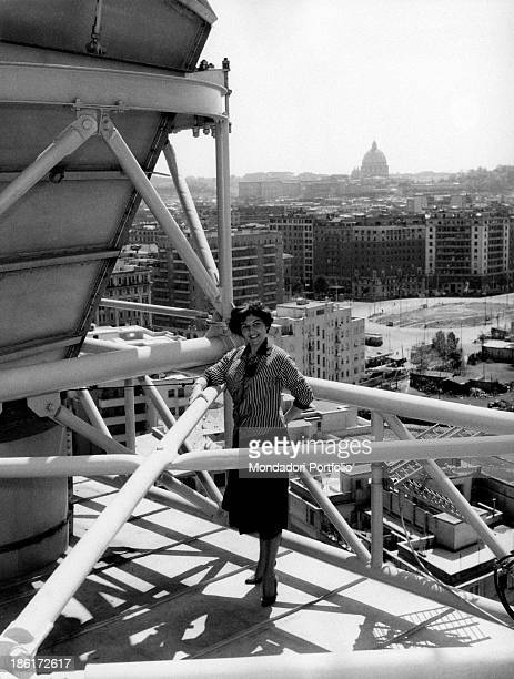 Italian actress Tatiana Farnese leaning on one of the pylons of the broadcasting horn antennas towering over the city Rome 1959