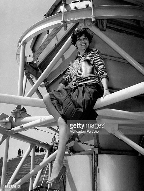 Italian actress Tatiana Farnese sitting on a TV antenna Rome 1959
