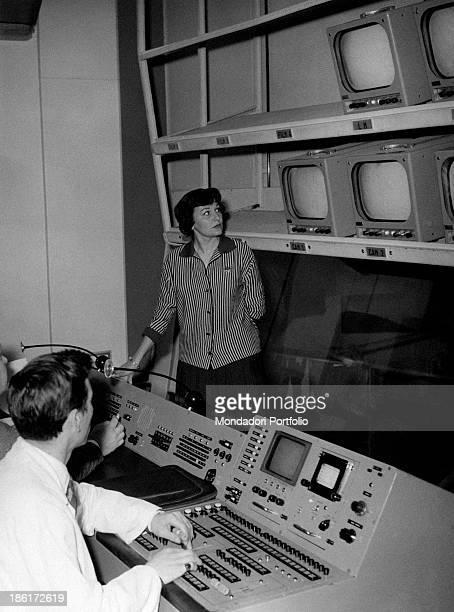 Italian actress Tatiana Farnese watching the screens in a TV direction room in company of Italian director Riccardo Mantoni Rome 1959