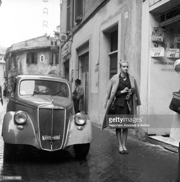 "Italian actress Valeria Ciangottini walking in the street beside a car in the film ""Family Diary"" directed by Italian director Valerio Zurlini. 1962"