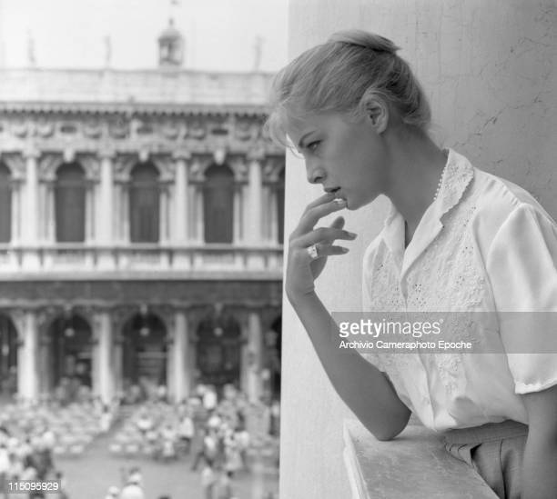 Italian actress Virna Lisi looking out the balcony of Palazzo Ducale in St Mark Square wearing an embroidered white shirt and a skirt her hair in a...