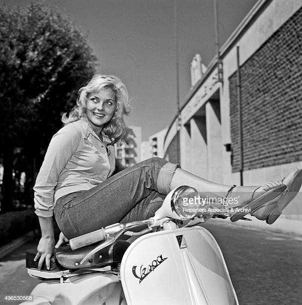 Italian actress Virna Lisi posing on a Vespa with her legs on the handlebars at the entrance of Cinecittà studios Rome 1957
