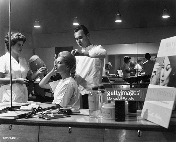 Italian actress Virna Lisi watching herself in the mirror while the hairdresser is completing her hairstyle Rome 1963