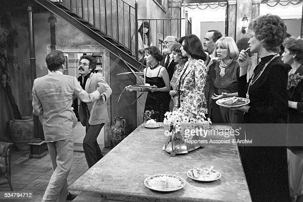 Italian actresses Milena Vukotic and Carla Gravina standing before two men fighting in the film The Terrace 1980