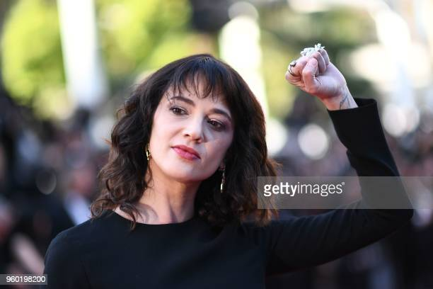 Italian actrses Asia Argento raises her fist as she arrives on May 19 2018 for the closing ceremony and the screening of the film The Man Who Killed...