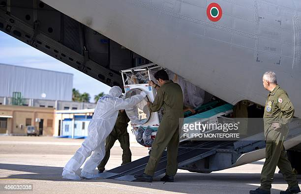 Italian aeronautical personnel wearing protective suits carry a pretended Ebola victim out of an Italian Air Force C130 military plane during a...