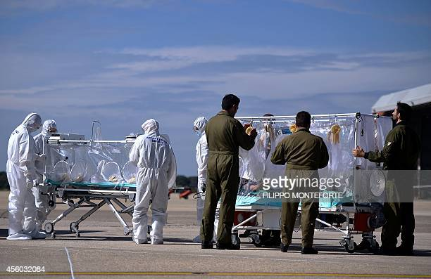 Italian aeronautical personnel wearing protective suits take care of a pretended Ebola victim during a specialized training course for the management...