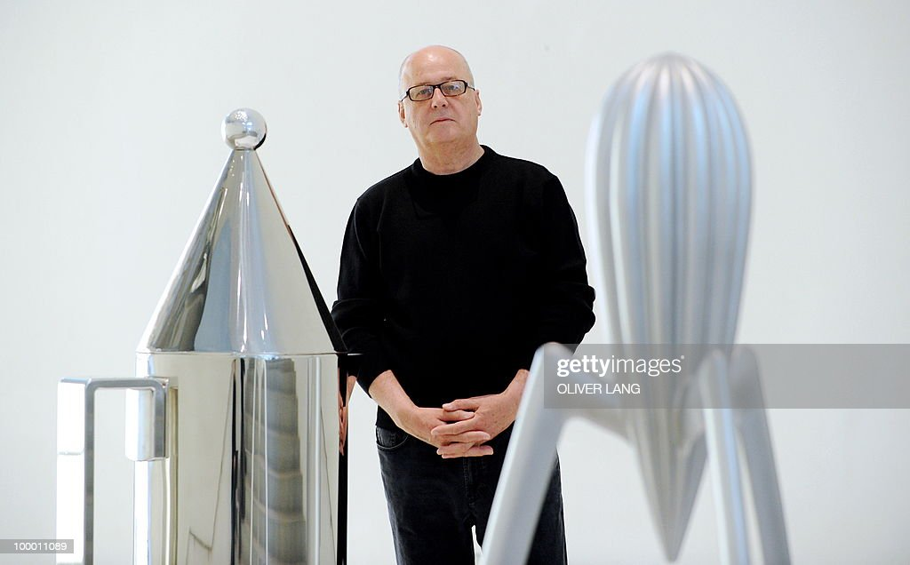 Italian Alberto Alessi, owner of the kitchen utensil company Alessi, poses between giant mockups of some of the company's products during a press preview of the exhibition 'Oggetti e Progetti - Alessi: storia e futuro di una fabbrica del design italiano' on May 20, 2010 at the Neue Sammlung (New Collection) museum in Munich, southern Germany. From May 22 to September 19, 2010, the museum presents a retrospective of the last 30 years of Italian design, focusing on a key player in the design world: the Alessi company.