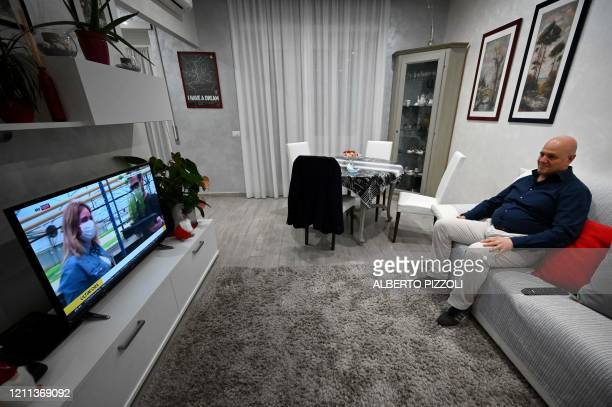 Italian anaesthesiologist Doctor Marino De Rosa watches TV as he rests on his couch at his apartment in Rome on April 29 2020 as the country faces a...