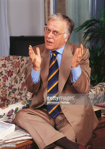 Italian anchorman and columnist Gianfranco Funari sitting on a coffee table at home 1993
