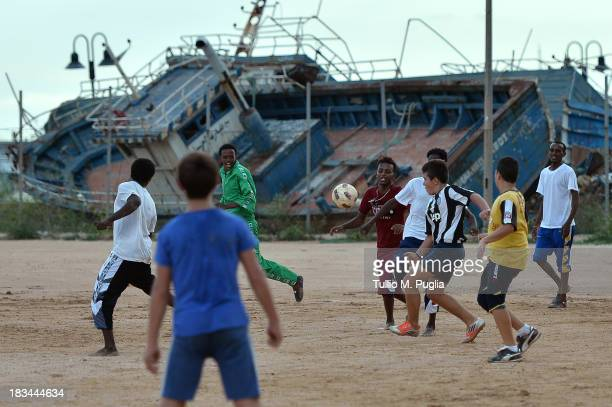 Italian and Eritrean migrant boys play football at Lampedusa Football Field where boats fomerly used by immigrants arriving in Lampedusa lie disused...