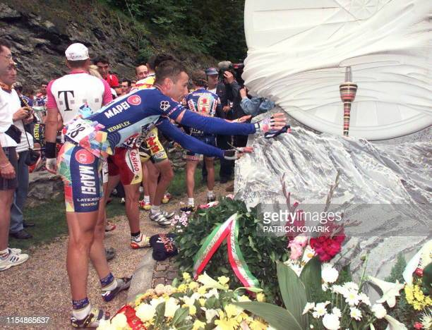 Italian Andrea Tafi touches the monument built in memory of compatriot Fabio Casartelli in the Portet d'Aspet pass near Luchon south of France 15...
