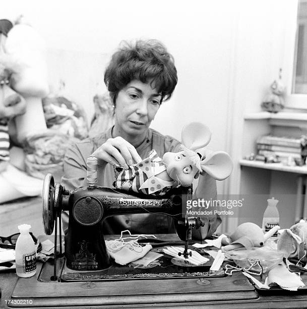 Italian animation artist Maria Perego inventor of Topo Gigio laying down a model of the famous puppet on a Singer sewing machine 1960s