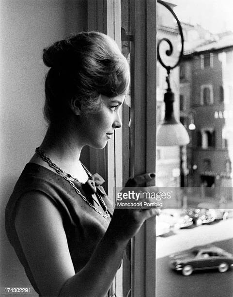 Italian announcer and presenter Aba Cercato the hair gathered up looks thoughtful out of the window where can be noticed a street crawling with cars...