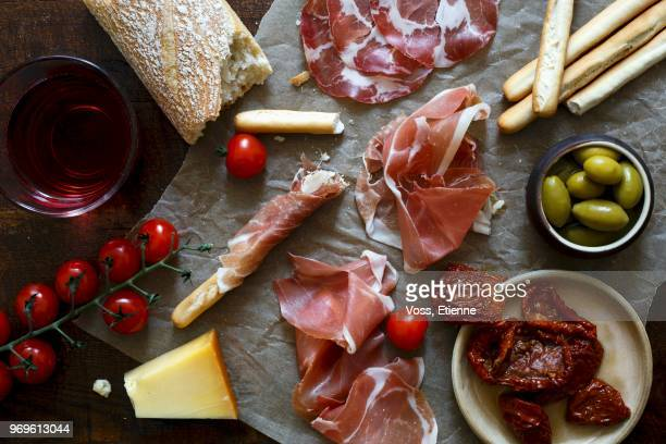 Italian antepasto spread on wrinkled wax paper and dark wooden board