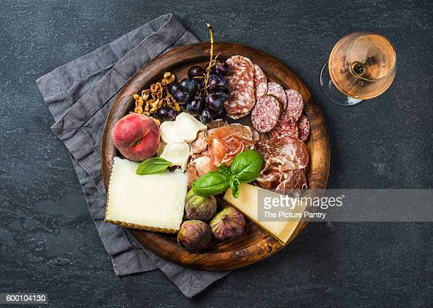 Italian antipasti snack for wine and glass of Rose on wooden serving tray over dark grunge background